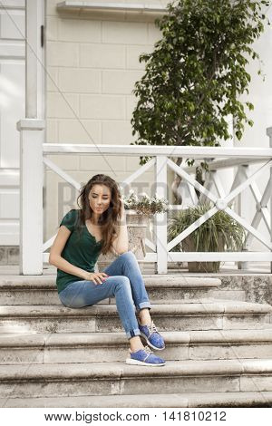 Young beautiful brown haired woman in blue jeans sitting on stone steps