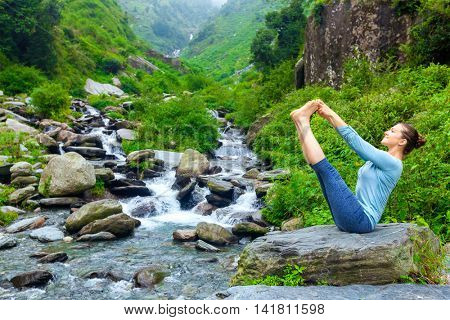 Yoga exercise outdoors -  woman doing Ashtanga Vinyasa Yoga balance asana Ubhaya padangusthasana Big Double Toe Yoga Pose at tropical waterfall in Himalayas in India