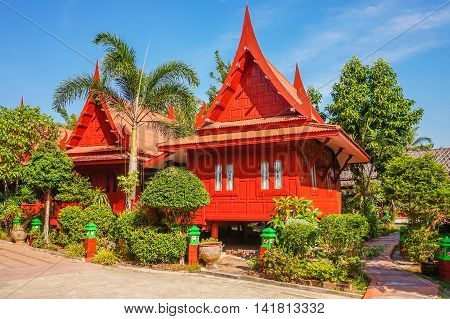 Thai house style, wood home in garden with many trees and blue sky, Thailand - colorful style