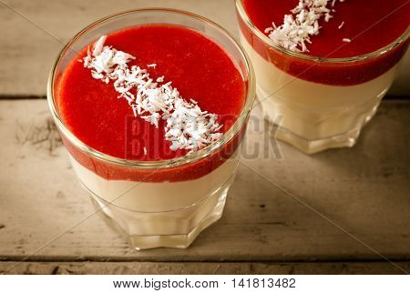 Creamy dessert with strawberry sauce and coconut flakes in glasses, on wooden background