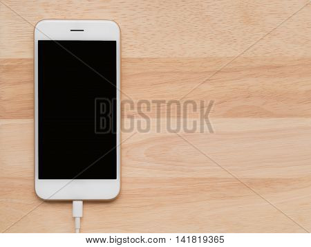 Top view (Flat Lay) of smart phone charging or connecting with USB cable on wooden texture background Copy space