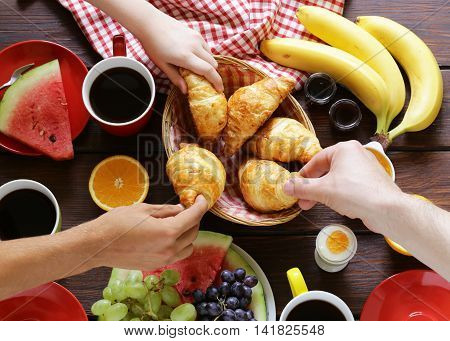 coffee, croissant and fruit breakfast on a wooden table, top view