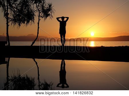 Contour of girl at the waterpool on the beach against the sunset at Balicasag island of Philippines