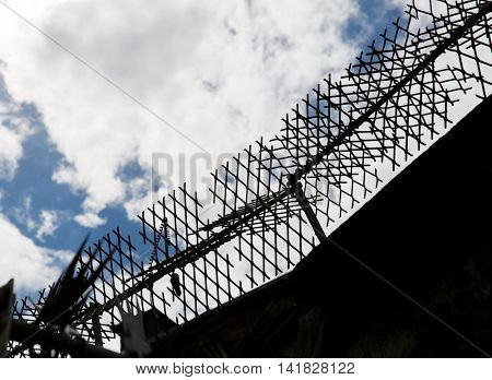 imprisonment concept - close up of fence with barbed wire and mesh in prison