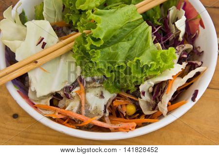 serving of healthy vegetables salad on wood table