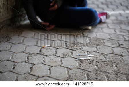 substance abuse, addiction, people and drug use concept - close up of addict woman and used syringes on ground