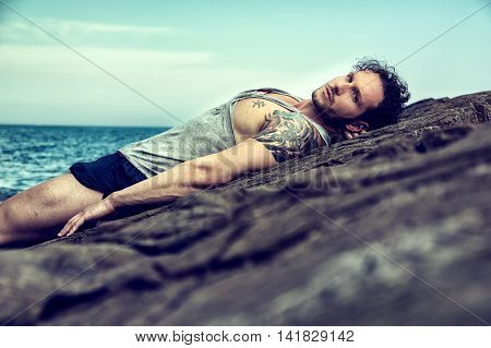 Handsome muscular man on the beach lying on rocks, looking at camera