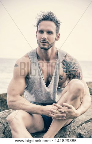 Handsome muscular man on the beach sitting on rocks, looking at camera