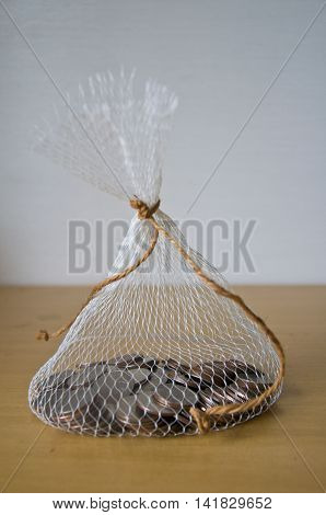 Thai coin in net bag on wood table