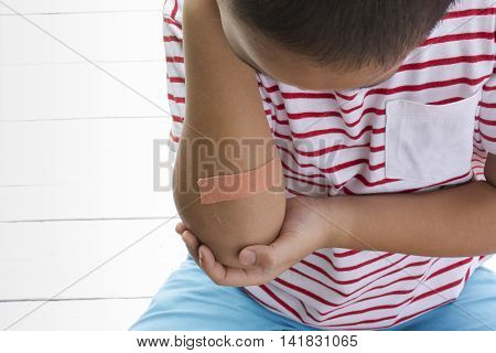 Children wound or The boy had an accident sitting on wooden white background.Top view and zoom in.1