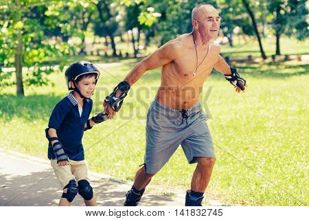 Grandfather Teaching His Grandson How To Roller Skate