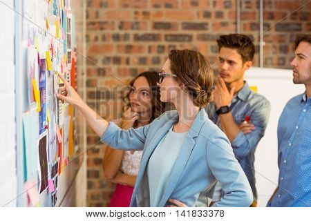 Business executives looking at sticky notes on whiteboard in office