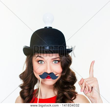 Happy comical young curly girl in amusing black hat with light bulb pointing up and using fake mustache props