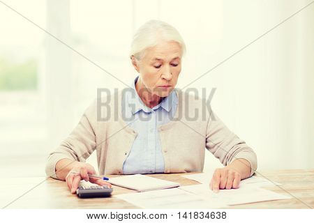 business, savings, annuity insurance, age and people concept - senior woman with papers or bills and calculator writing at home