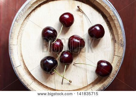 Farm concept. Few cherry fruits in a row on top of oak barrel