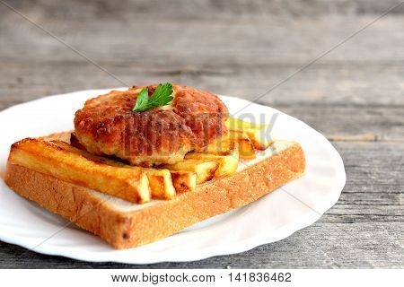 Sandwich with fried potatoes and meat cutlet on a plate and on old wooden table. A sandwich cooked from slice of white bread, fried potatoes and Turkey burger. Closeup