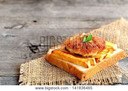 Sandwich with fried potatoes and meat cutlet on a burlap and on old wooden table for empty space for text. A sandwich cooked from slice of white bread, fried potatoes and Turkey cutlet