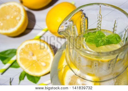 Lemon and lemonade on white wooden table