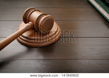 Judge hammer on brown lacquered wooden desk close up with copy space. Legislation Concept