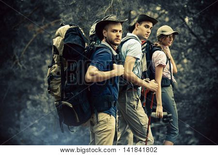 Adventure and hiking. Group of young people make a hike in mountains. Active lifestyle. Tourist equipment.