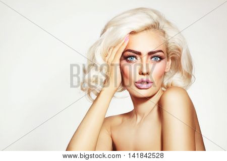 Vintage style portrait of young beautiful tanned sensual platinum blonde girl with stylish make-up and hairdo