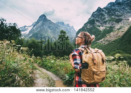 Hiker with backpack looking at mountains, alpine view