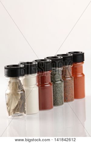 Various spices in small glass bottles, close up