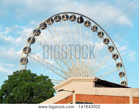 The tall ferris wheel in the park.