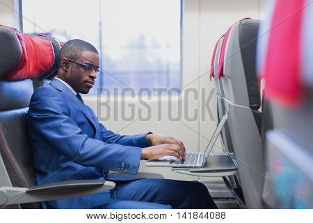 Young businessman with laptop in a train