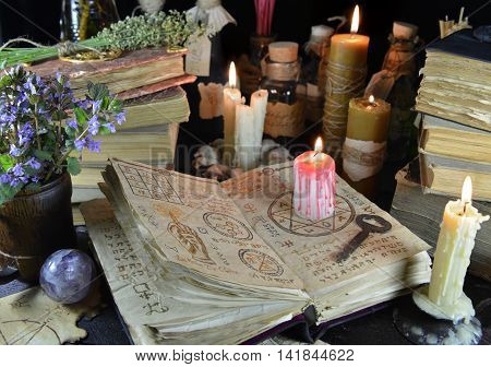Witch table. Halloween still life with book, magic objects and burning candle. Signs on pages of the open book are not foreign text, these letters are imaginary, fictional symbols only.