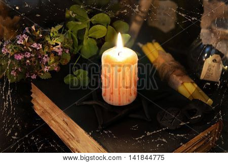 Textured and filtered Halloween image with bloody candle on black magic book
