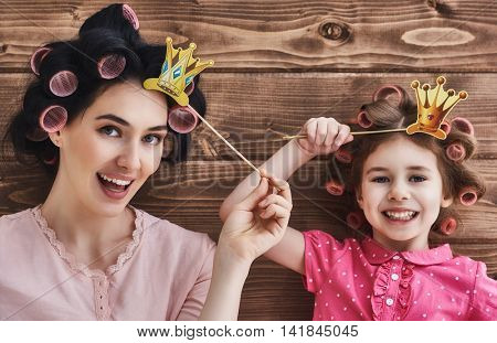 Funny family! Mother and her child daughter girl with a paper accessories. Beauty funny kid and mommy holding paper crown on stick.