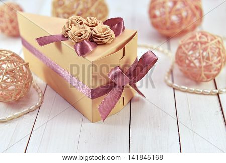 Present in the decorated triangle gift box with trinkets on wooden planks, holiday still life