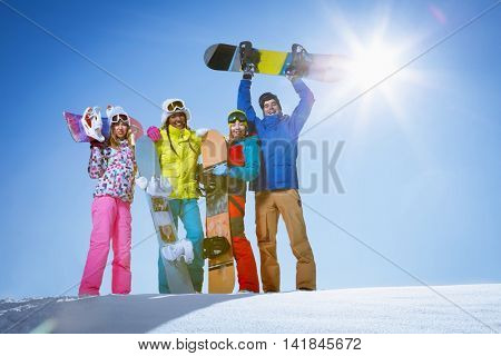 Young smiling people with snowboards