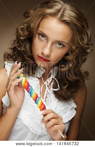 Young pretty woman with colorful lollipop