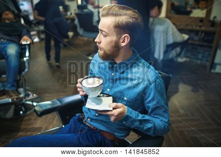 Young man with cup indoors