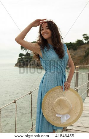 Young woman with summer hat posing on the bridge, happy vacation