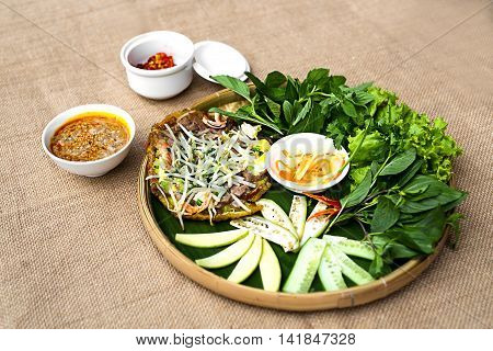 Vietnamese plain rice flan or banh khoai Hue with herbs and special sauces