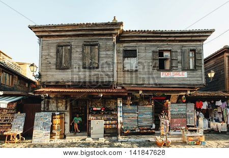 NESSEBAR BULGARIA - AUGUST 31 2015: Souvenirs seller sits in his shop in the old part of Nessebar. The ramshackle building for sale in Old Town.