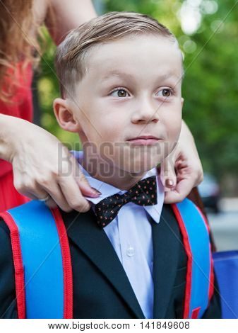 Mom corrects bow tie to his son first graders mother's hands blurred in motion