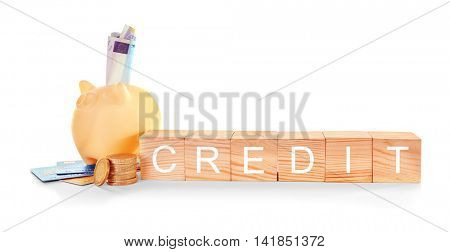 Wooden cubes with word Credit, coins and piggy bank on white background