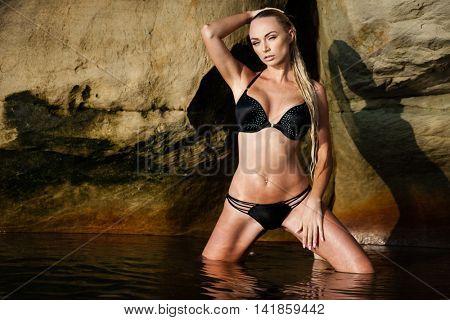 Sexy blond girl in black bikini posing on a beach