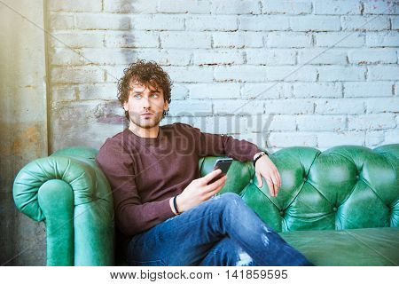Pensive curly thoughtful attractive young handsome man in brown sweetshirt and jeans sitting on green leather sofa hoding cellphone