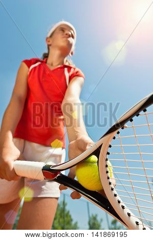 Young female serving ball on tennis match