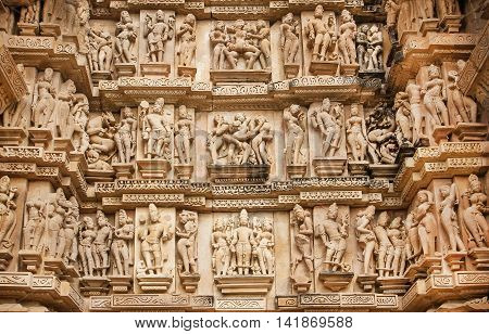 Famous historic monumant with erotic theme on sculptured wall of indian temple of Khajuraho. UNESCO Heritage site built between 950 and 1150 in India, belong to two religions - Hinduism and Jainism.