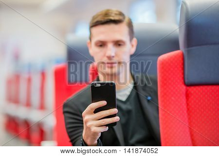 Tourist writes a message on his phone while traveling by express train