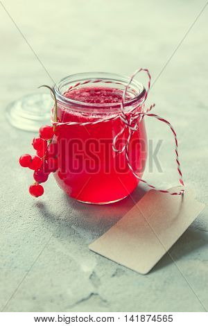 Homemade red currant jam or syrup on a stone background. Closeup toned