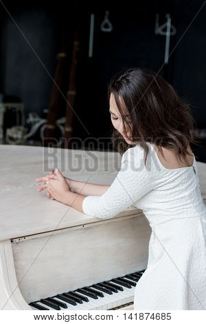 beautiful brunette girl standing at a piano. professional model
