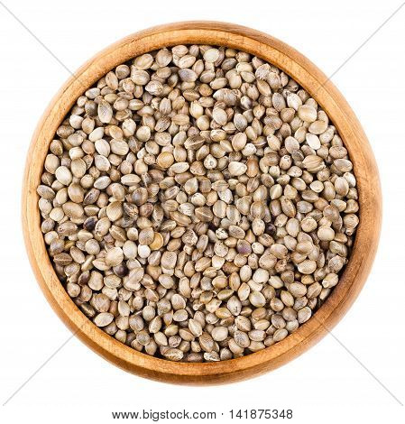 Hemp seeds in a wooden bowl on white background. Unshelled edible raw hempseeds of Cannabis sativa. Isolated close up macro photo from above.