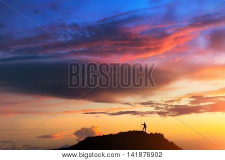 At the top of the world. A person is standing on the hill beneath colorful sky at the sunset. Clicked on the top of Batur volcano (Bali Indonesia).